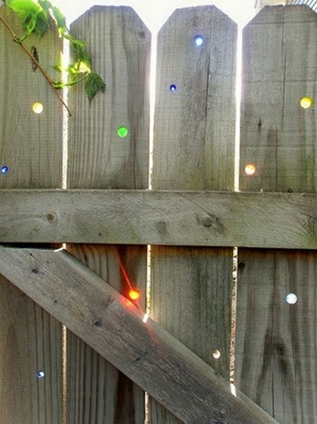 18 Upcycling Ideas - Have holes in your fence? Use marbles to plug them up.