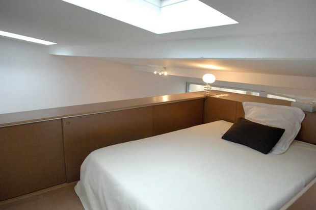 Epic Garage Conversion - The bedroom sits atop the wooden furniture piece and even has a gorgeous skylight!