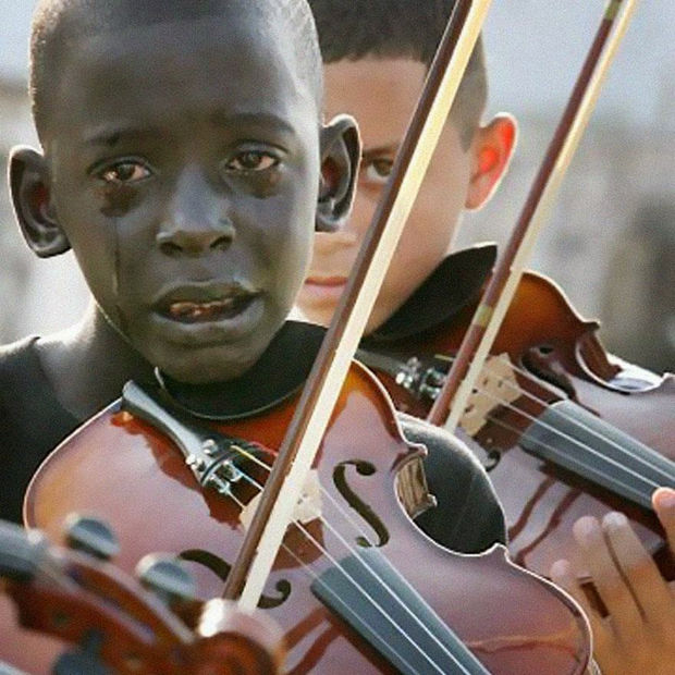 29 Powerful Pictures - Diego Frazão Torquato, a 12-year-old Brazilian, tears up while playing the violin at his teacher's funeral. The teacher had helped him escape violence and poverty through music.
