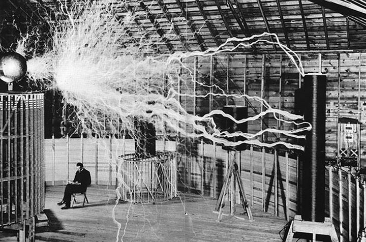 "21 Historical Photos - Nikola Tesla, electrical engineering pioneer, sitting in his laboratory with his ""Magnifying Transmitter""."