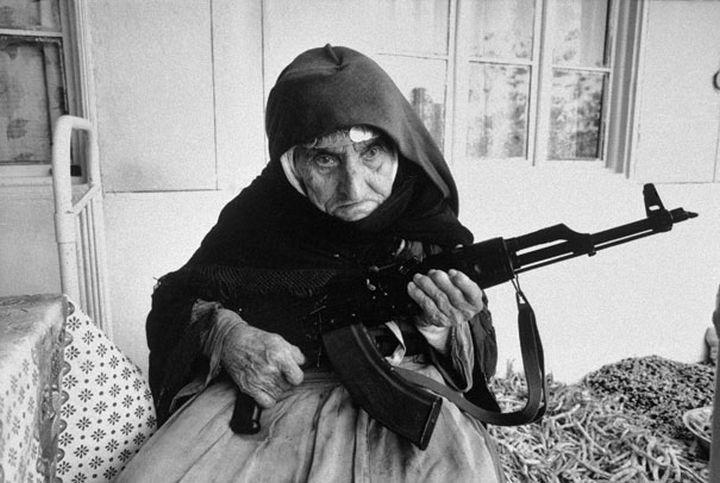 21 Historical Photos - 106-year-old woman guards her home with a rifle, in Degh village, near the city of Goris in southern Armenia, 1990.