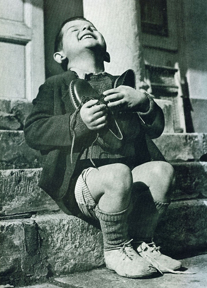 21 Historical Photos - A six year-old boy at an orphanage in Austria hugs his new pair of shoes given to him by the American Red Cross during World War II.