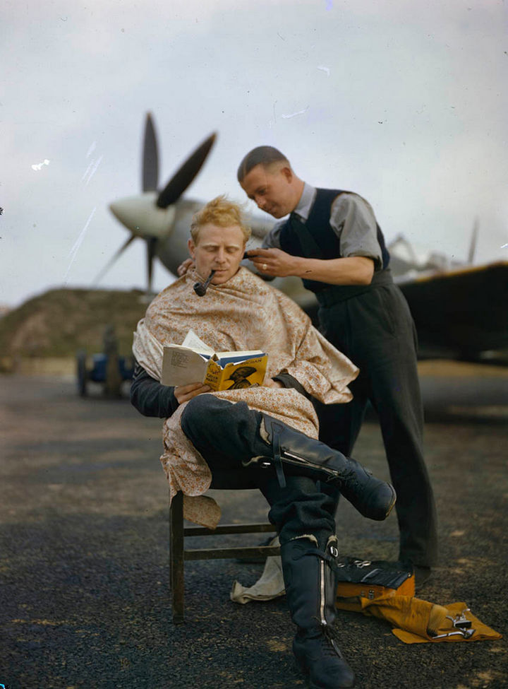 58 Colorized Photos from the Past - An RAF pilot getting a haircut between missions while reading a book.