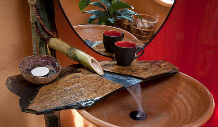 A bamboo waterfall faucet and sink made from natural materials.