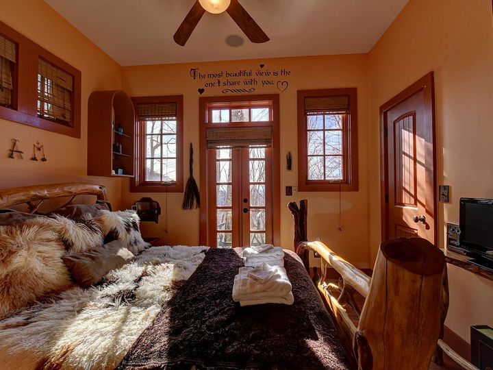 "The main bedroom features a king-sized bed with a heartwarming message above the door, ""The most beautiful view is the one I share with you""."