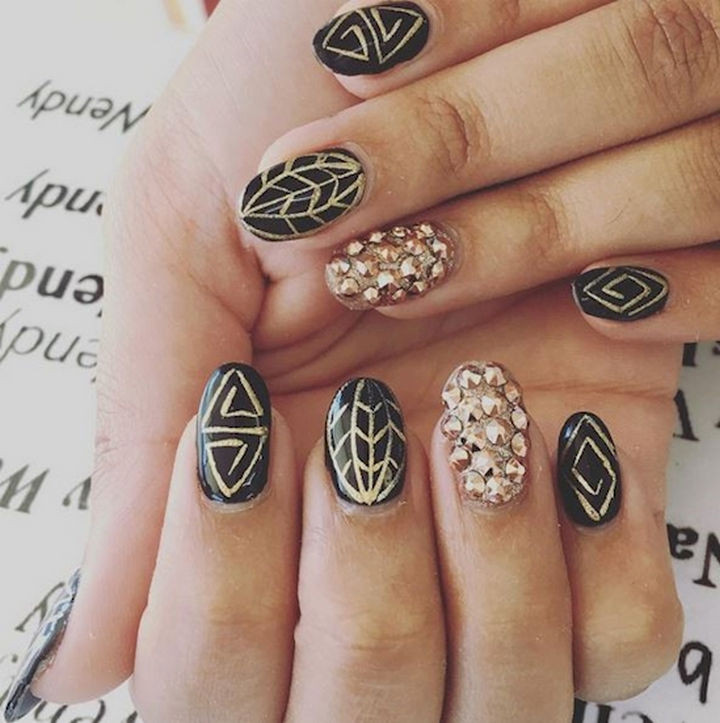22 Black Nails That Look Edgy and Chic - The elegance of black with intricate rose gold art.