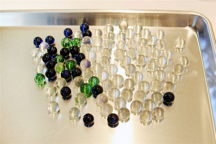 Other than supplies, you will also need a baking sheet, a bowl filled with ice water, and an oven to heat the marbles.