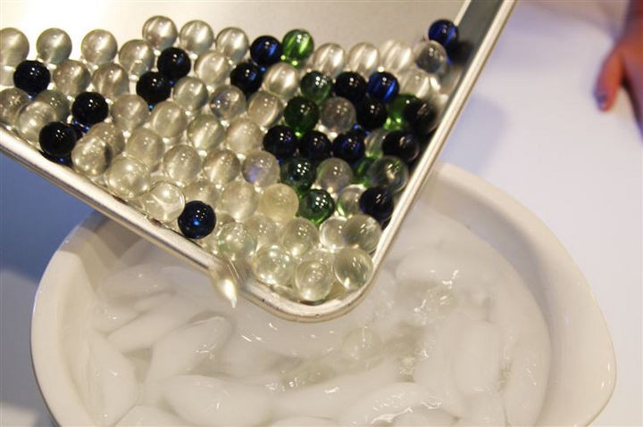 Have a bowl of ice water ready when you pull them out of the oven. Carefully dump the marbles into the ice water.
