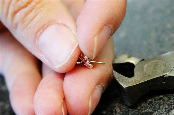 With cutters or pliers, trim just enough of the pin to allow you to bend it into a loop to secure the bead cap.