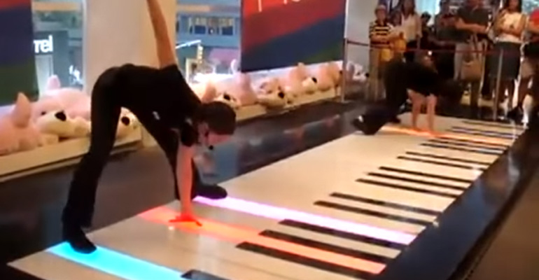Two Women Playing Bach's Toccata in D on a Floor Piano.