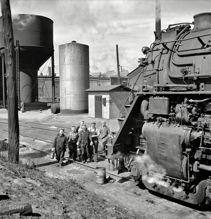 35 Rare Historical Photos - 1943: Women wipers cleaning an engine at the Chicago & North Western Railroad in Clinton, Iowa.