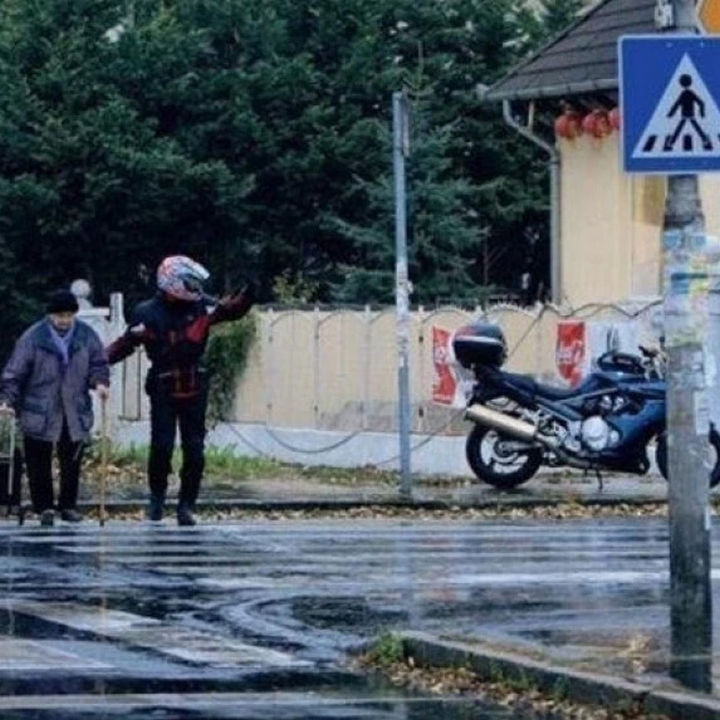 15 Incredible Photos Will Warm Your Heart - A man getting off his motorcycle to help an elderly pedestrian cross the street.