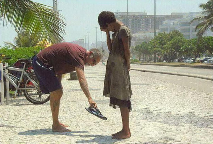 15 Incredible Photos Will Warm Your Heart - A man giving his sandals to a woman in need in Rio De Janeiro.