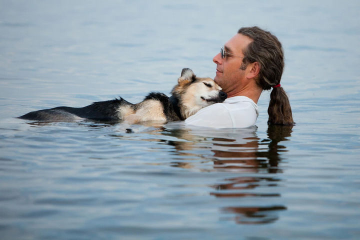 15 Incredible Photos Will Warm Your Heart - John Unger cradles his 19-year-old dog Schoep to sleep every night in Lake Superior to ease his dog'sarthritic pain.