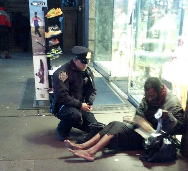 15 Incredible Photos Will Warm Your Heart - A tourist captured this incredible photo of an NYPD officer offering warm boots and thermal socks to a homeless man on a cold evening.