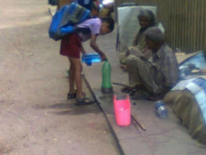 15 Incredible Photos Will Warm Your Heart - A young boy offering fresh water to a homeless couple.