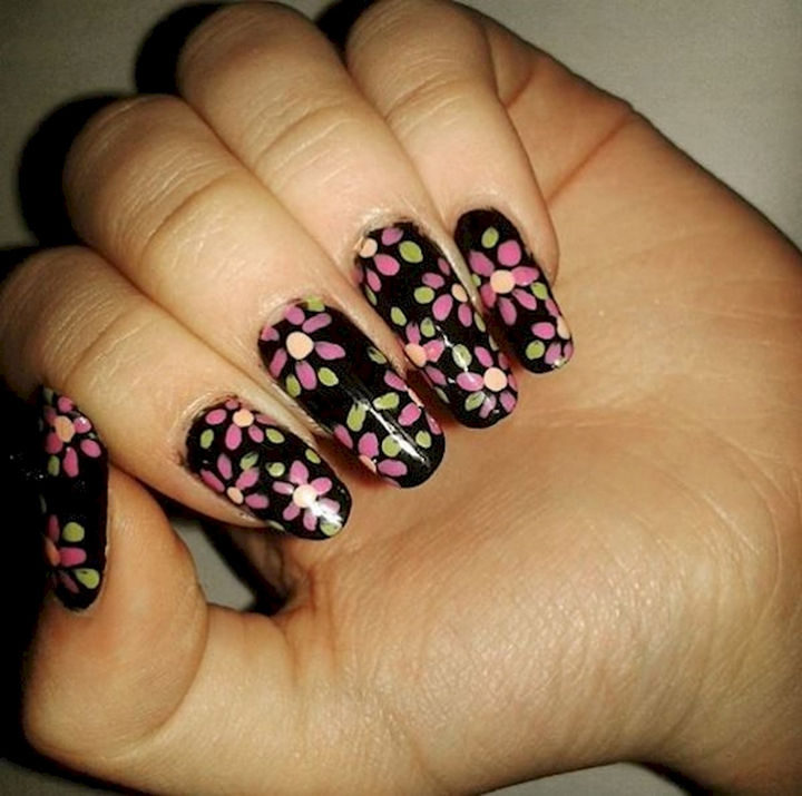 Great contrast with colorful floral nails on a black backdrop.