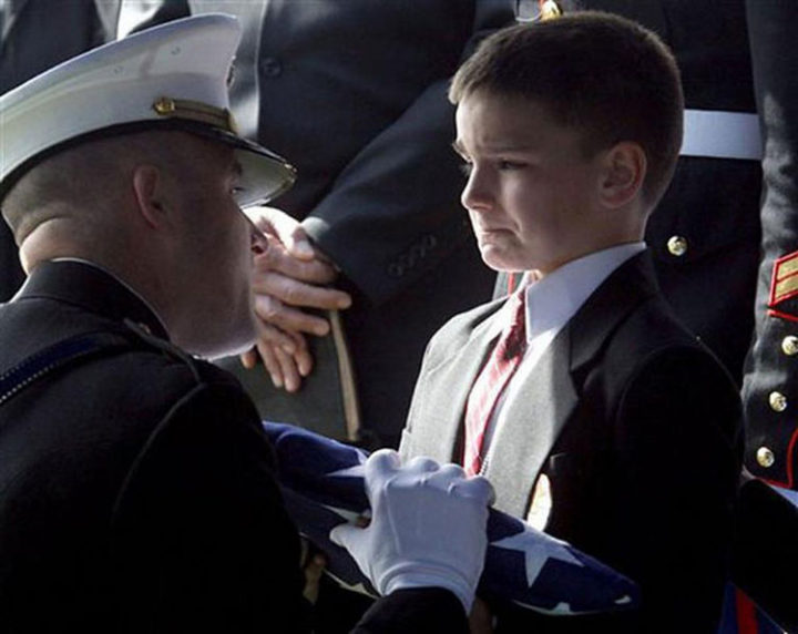 9 Heartbreaking Images - An emotional little boy is given the U.S. flag during his soldier father's funeral.