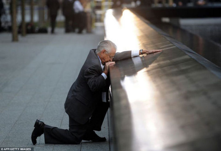 9 Heartbreaking Images - This man kneels at the 9/11 memorial over the loss of his son.
