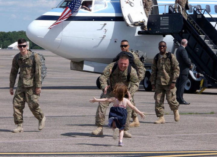 15 Emotional Photos of Soldiers Coming Home - A joyful daughter reuniting withher father.