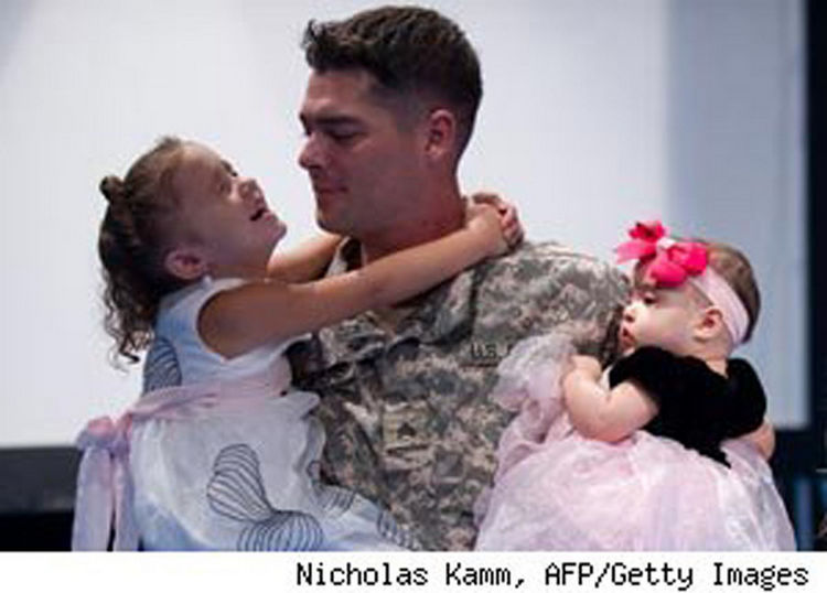 15 Emotional Photos of Soldiers Coming Home - A proud father reuniting with his two beautiful daughters.