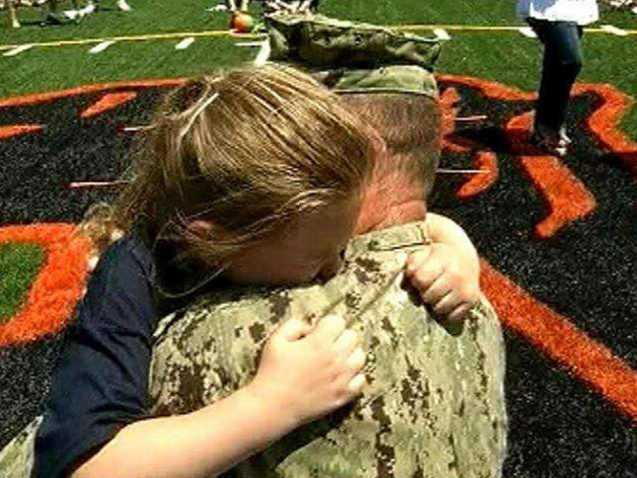 15 Emotional Photos of Soldiers Coming Home - A loving father and daughterhugging each other.