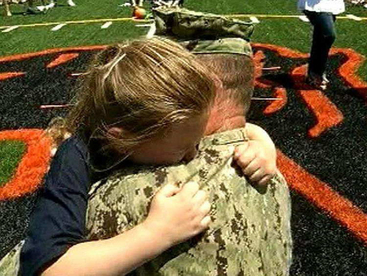 15 Emotional Photos of Soldiers Coming Home - A loving father and daughter hugging each other.