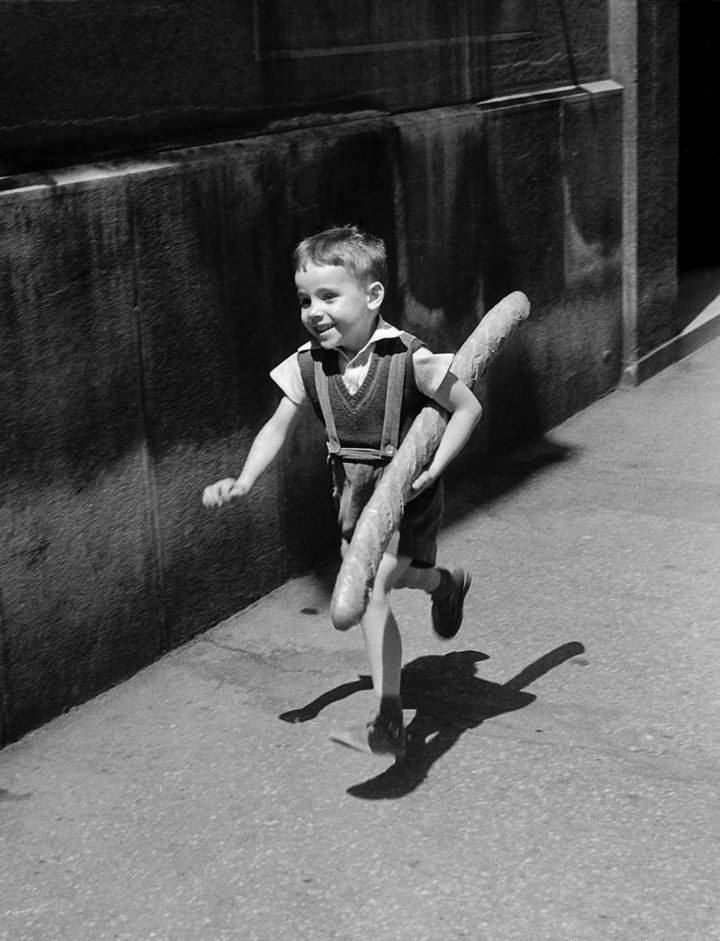 22 Timeless Images - A little boy in Paris running home for dinner with a freshly-baked baguette (1952).