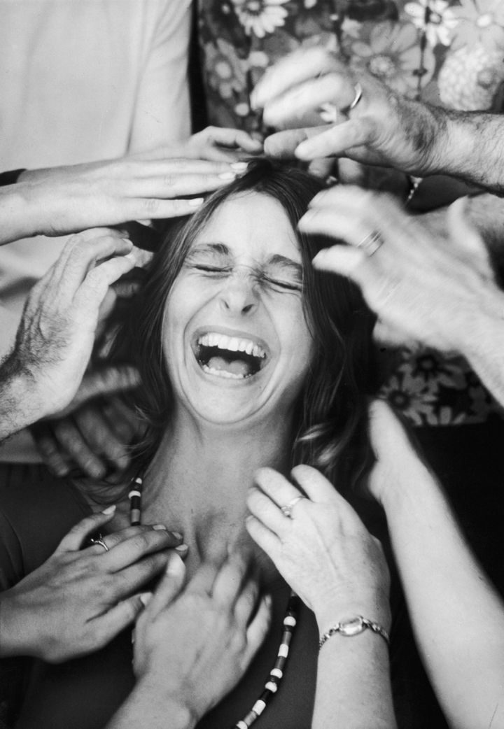 """22 Timeless Images - A woman roaring with laughter as she undergoes a """"head-tapping session"""" during a sensory awareness class in Big Sur, California (1970)."""