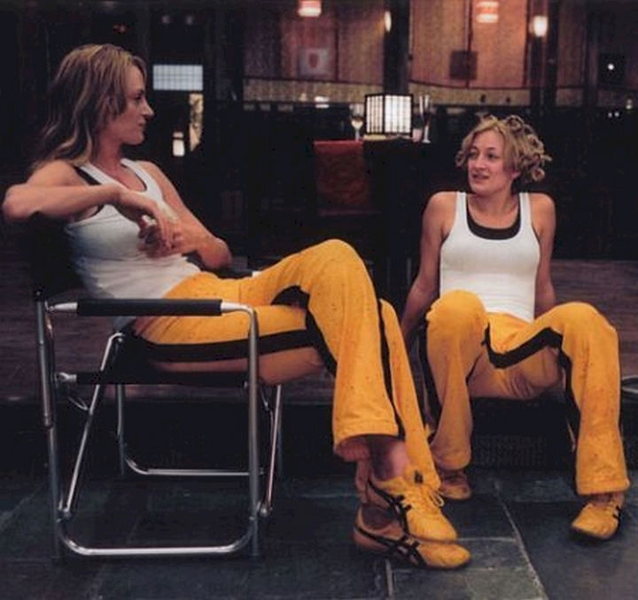 "23 Celebrities Hanging Out With Their Stunt Doubles - Uma Thurman sits with her stunt double on the set of ""Kill Bill: Volume 1."""