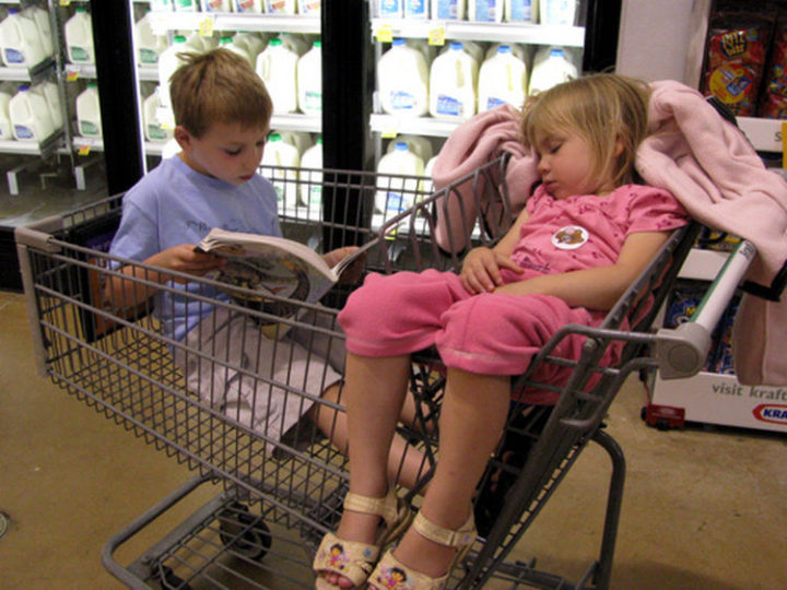 25 Kids Sleeping in the Strangest Places - Big brother reading a bedtime story.