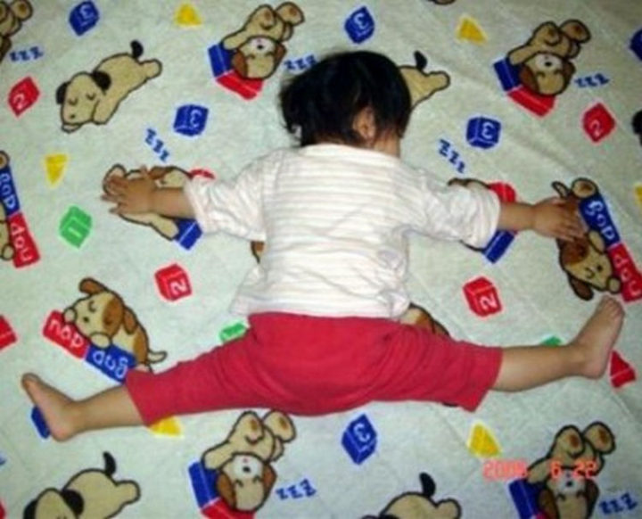 "25 Kids Sleeping in the Strangest Places - She loves her bed ""this much."""