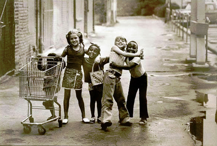 In July 1973, Joseph Crachiola captured a spontaneous moment of 5 childhood friends hugging each other while walking the streets of Mount Clemens, Michigan.