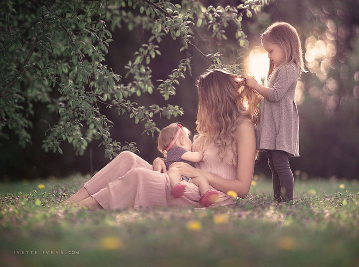 Breastfeeding is a family affair and pictured is thoughtful daughter braiding her mother's hair while mom is feeding her little sister.