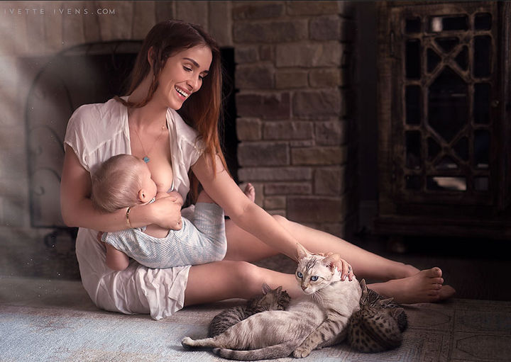 A beautiful photo of a mother feeding her baby alongside a cat nursing her young.