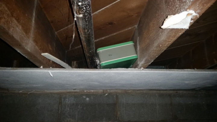After removing another piece, he noticed a strange metal box tucked within the wooden beams.