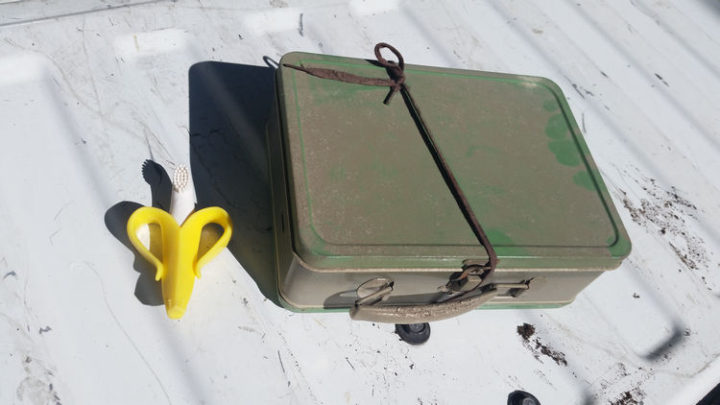 The box was covered in dust and looked very old. It was secured with a shoelace and he placed a plastic banana beside it for scale.