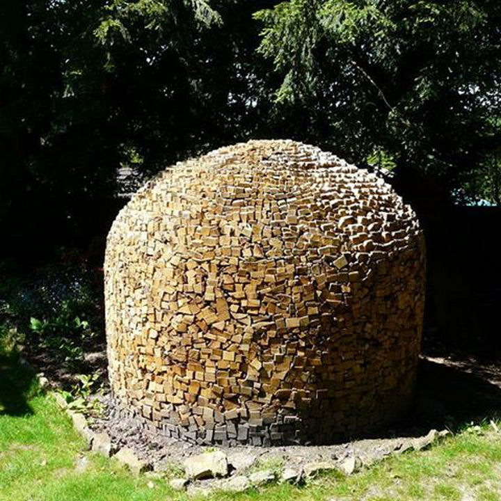 13 Displays of Stacked Wood Art - A log pile shaped like a bee hive.