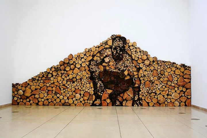 13 Displays of Stacked Wood Art - The man inside the wood pile.