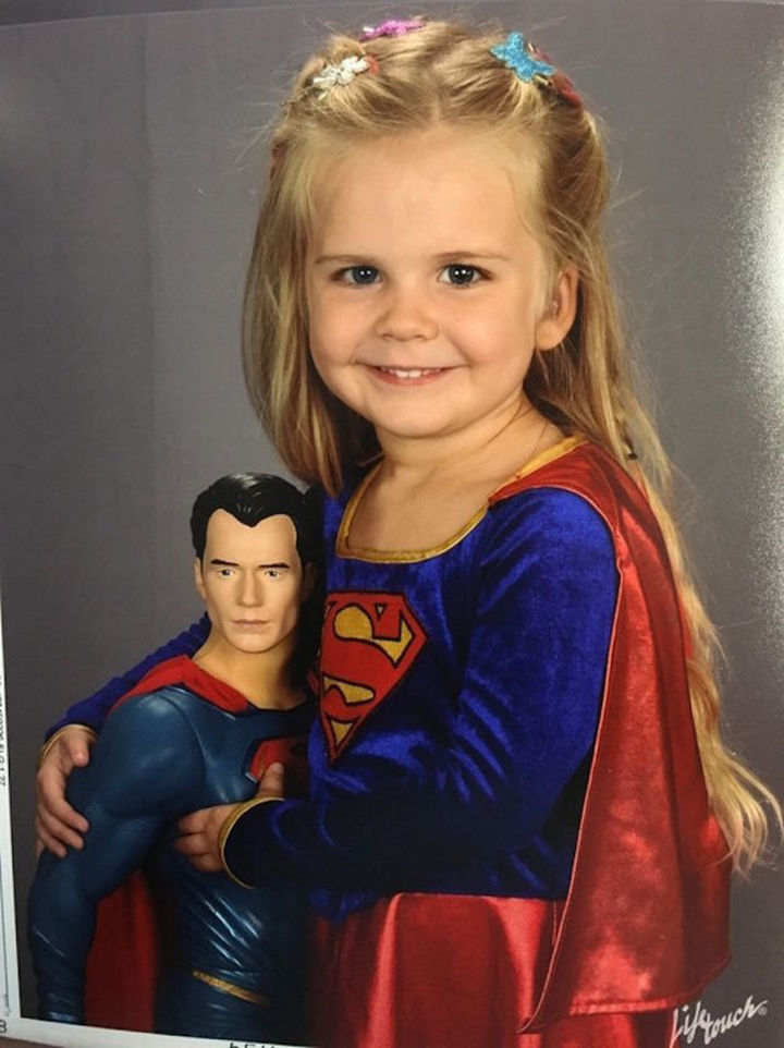She dressed up as Supergirl and held on to her Superman doll. Her father posted the photo on Reddit and it quickly went viral.