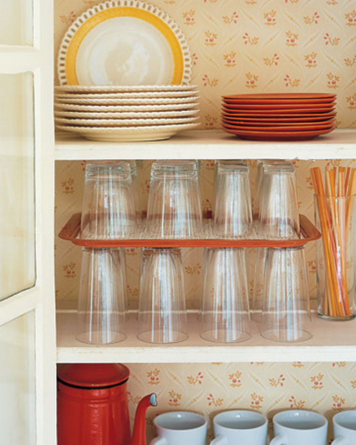 18 DIY Storage Ideas For Your Home - Increase your cupboard space by using a serving tray as a shelf divider for glasses and other small items.
