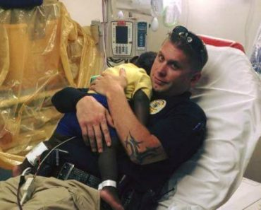 Officer James Hurst Comforts Crying Child During Medical Exam.