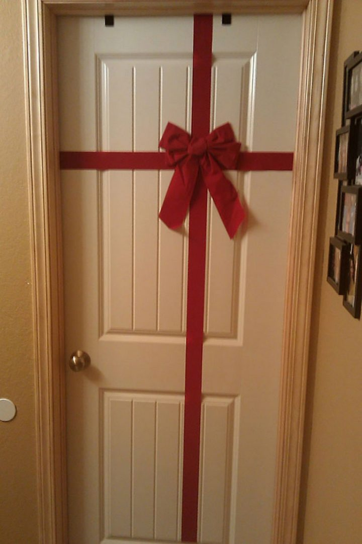 27 Lazy Christmas Decoration Ideas - This Christmas present door decoration looks good too.