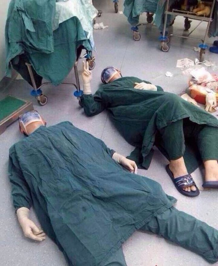 Two surgeons resting after a 32-hour surgery to remove a set of brain tumors.