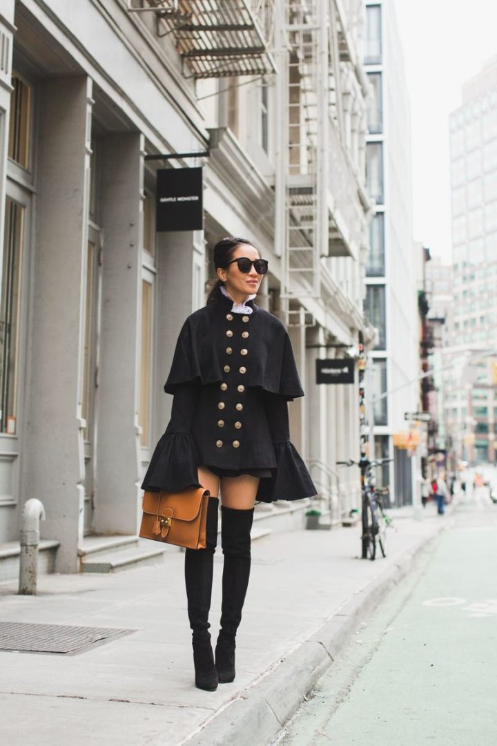 Wear capes like blogger Wendy Nguyen, who has on a pair of knee-high boots and a light brown satchel envelope to complete the outfit.