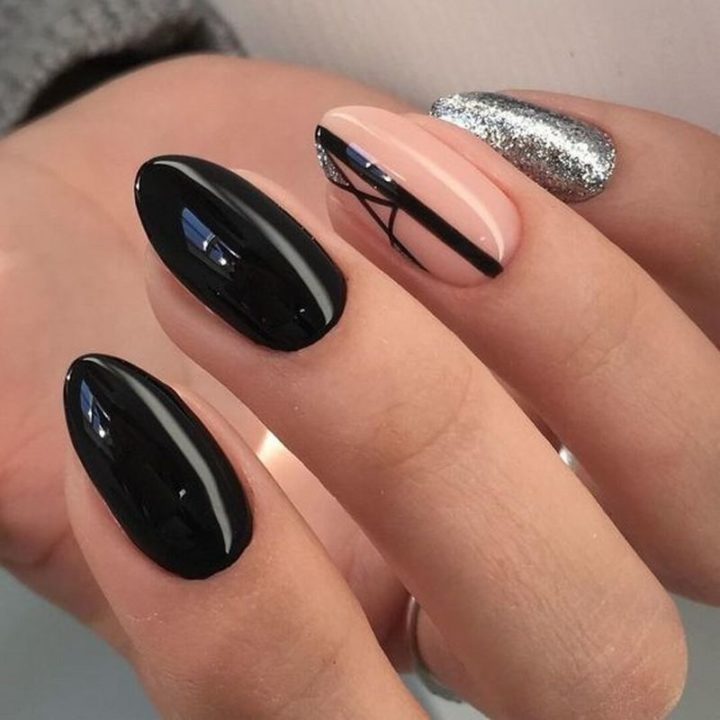 Black glossy nails with intriguing beige nail art.